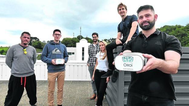 Iñaki Aramburu, en el centro, y Jorge Maylin, a la derecha, muestran las gafas de realidad rodeados del equipo de Oroi. / FÉLIX MORQUECHO
